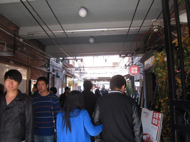 泰康路に面して並ぶ商店の間に、1階部分がポッカリとあいた通路がある。中へ入っていくと、そこが田子坊だ。