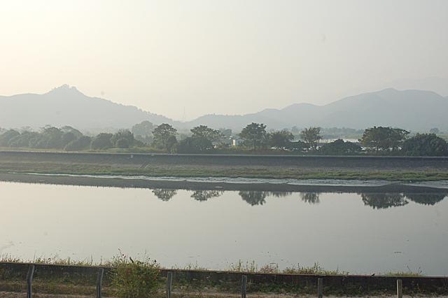 川の向こう側に広がる香港の田園と山岳地帯