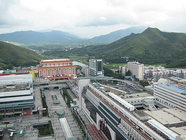 深圳側から見た羅湖口岸(中央やや左にあるベージュ色の建物)。向こう側に見える山々が香港側で、手前右に見えるのが深圳駅